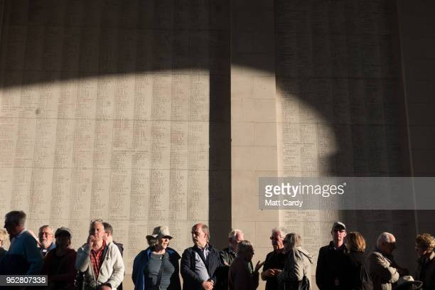 People stand below the names of the fallen inscribed on the Menin Gate Memorial as they gather for the Last Post ceremony at the Menin Gate on April...
