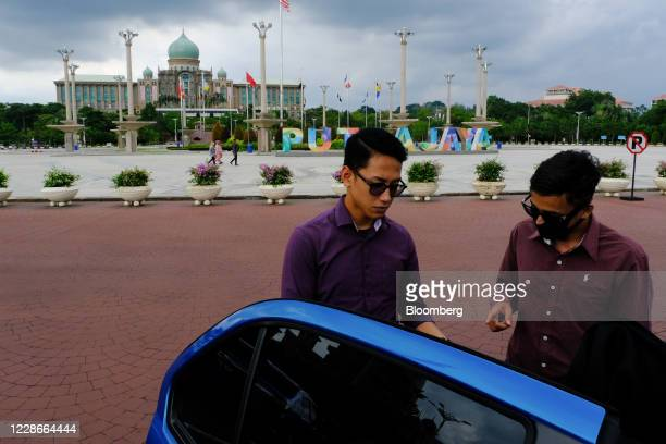People stand beside a car near the Perdana Putra the office complex of the Prime Minister of Malaysia in Putrajaya Malaysia on Wednesday Sept 23 2020...