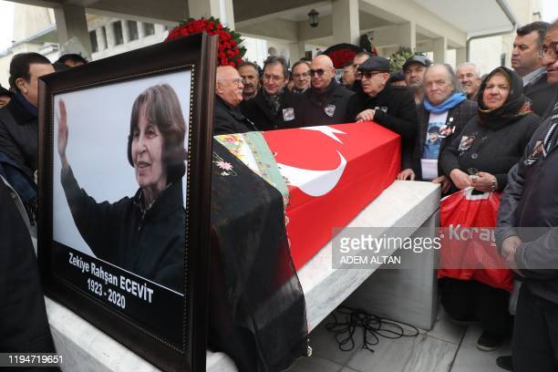 People stand beside the coffin of Rahsan Ecevit, wife of late Turkish Prime Minister Bulent Ecevit, during her funeral ceremony at the Kocatepe...
