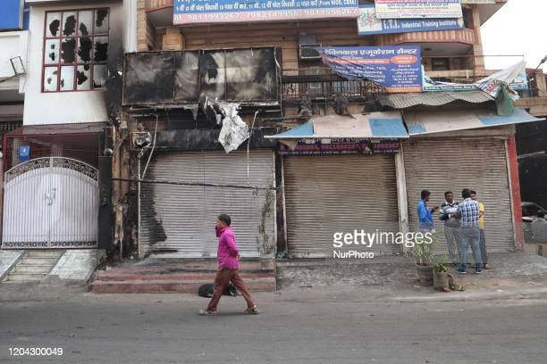 People stand besides burnt building after it was set on fire by a mob during riots in Chandbagh area of New Delhi India on 29 February 2020 More than...