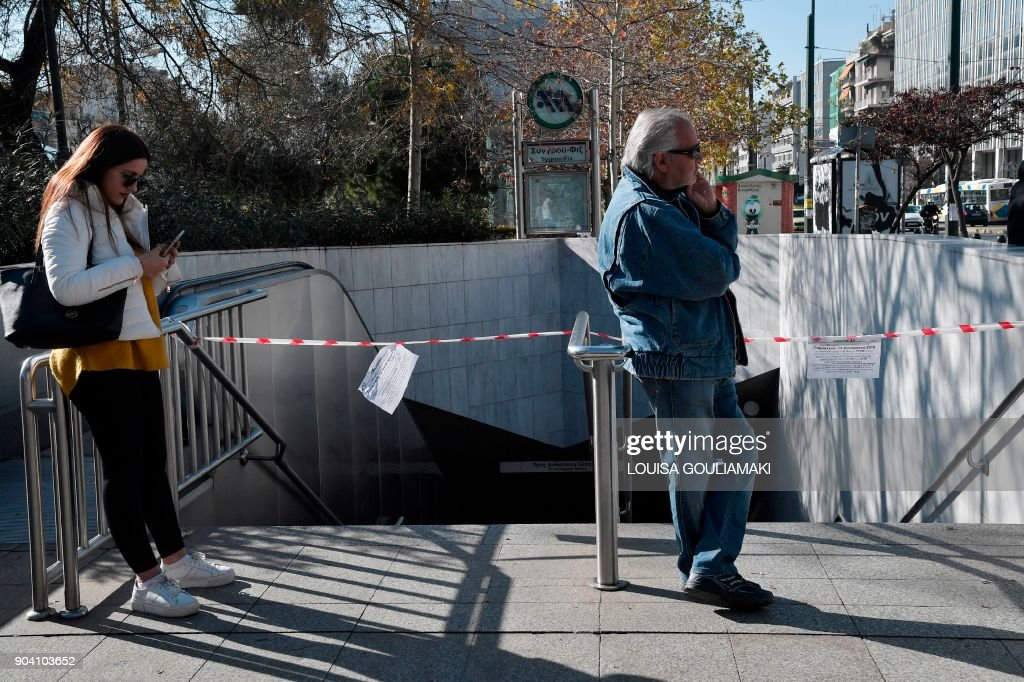 People stand by a cordoned off closed metro station in Athens due to 24-hours strike on January 12, 2018. Greek unions call one-day national strike to protest changes to a labour law demanded by the country's creditors. GOULIAMAKI