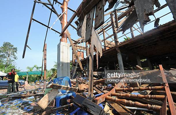 People stand by a damaged house following a deadly exchange of gunfire between Thai and Cambodian soldiers at Kap Choeng district in Surin province...