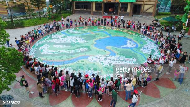 People stand by a huge earth painting on the Earth Day on April 22 2018 in Foshan Guangdong Province of China Nearly 2000 people from 490 families...