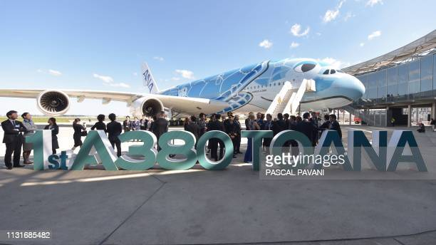 People stand by a Japanese airline All Nippon Airways ANA Airbus A380 during a ceremony for the delivery of the company's first Airbus A380 on March...