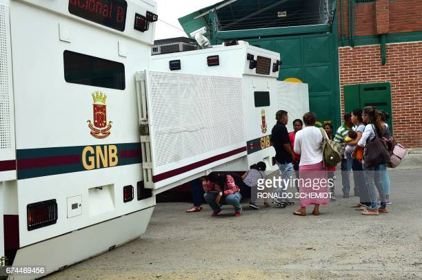 People stand by a National Guard riot control vehicle placed in front of the Ramo Verde prison in Los Teques 30 km east of Caracas where opposition...