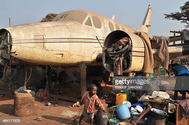 People stand by a plane in the camp for displaced persons at the Mpoko airport in Bangui on January 21 a day after the election of Catherine...