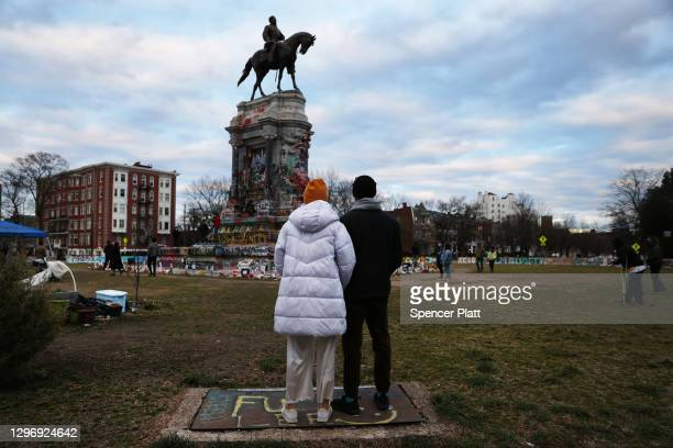 People stand by a statue of Robert E. Lee on January 17, 2021 in Richmond, Virginia. The statue has become a focal point of the Black Lives Matter...