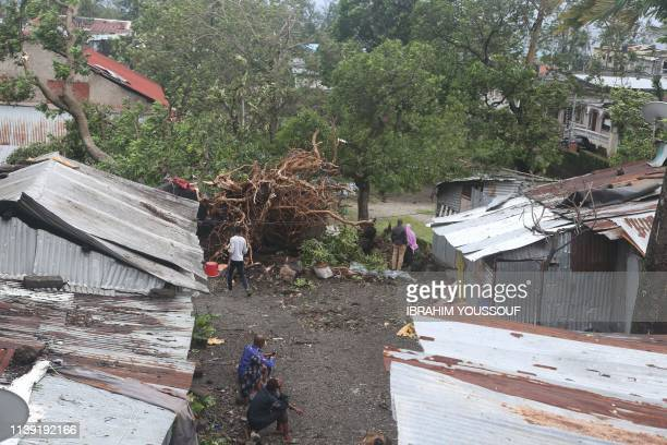 People stand by damaged houses and fallen trees on April 25, 2019 in Moroni after tropical storm Kenneth hit Comoros before heading to recently...