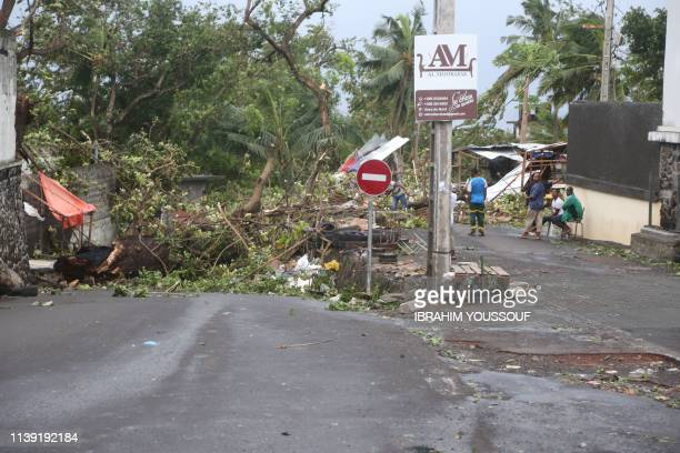 People stand by fallen trees on April 25, 2019 in Moroni after tropical storm Kenneth hit Comoros before heading to recently cyclone-ravaged...