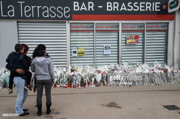People stand by flowers laid in front of Alexia Daval parents' restaurant on November 2 2017 in Gray eastern France in tribute to Alexia Daval whose...