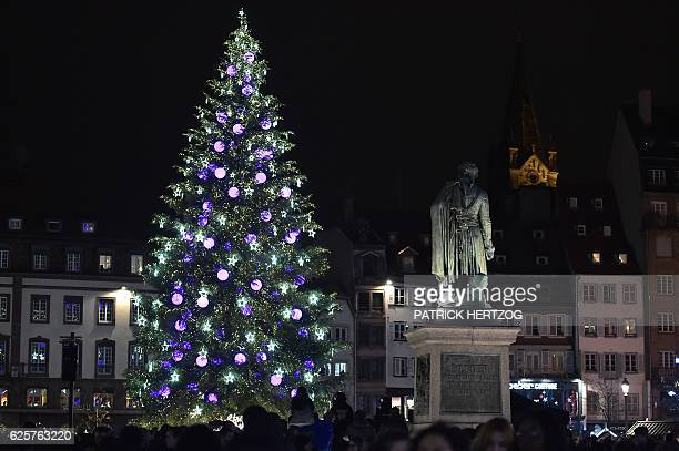 People stand by the decorated Christmas tree at the Christmas market in Strasbourg during the opening day in Strasbourg eastern France on November 25...