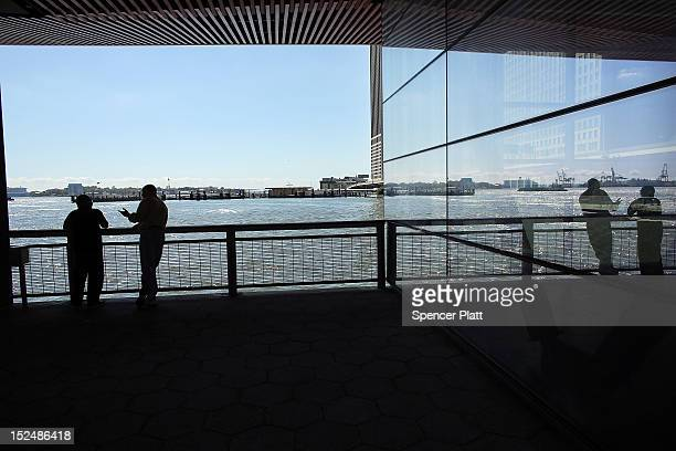 People stand by the East River on the last day of summer on September 21, 2012 in New York City. The summer of 2012 saw a continuing pattern of...