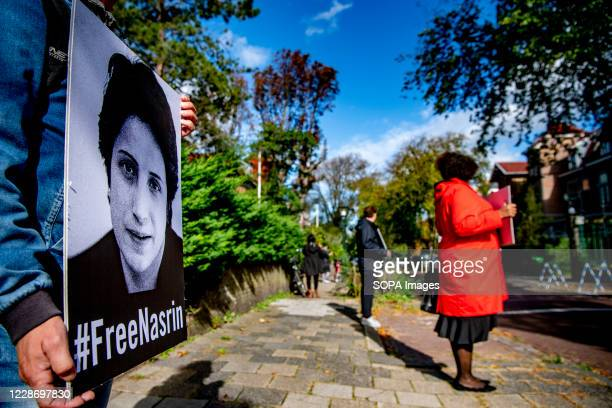 People stand displaying placards with a message stating Free Nasrin Now in The Hague Amnesty International calls on the Iranian authorities at the...