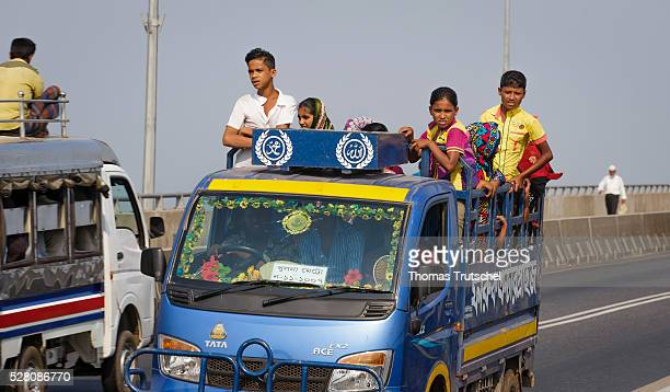 People stand during a drive on the load area of a transporter on April 11 2016 in Khulna Bangladesh