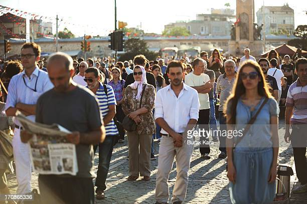 People stand during a silent protest in Taksim Square June 19 2013 in Istanbul Turkey Performance artist Erdem Gunduz nicknamed The Standing Man...