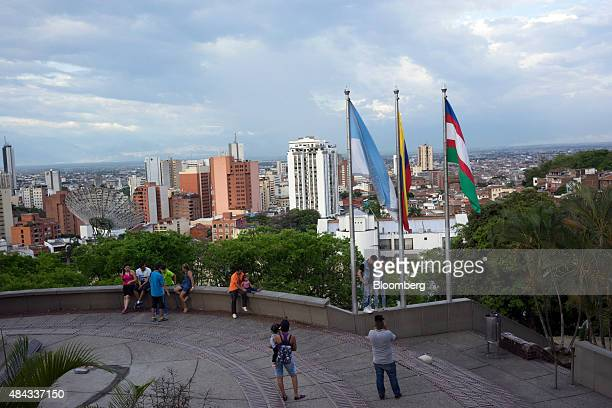 People stand for photographs in a plaza over looking Cali Colombia on Wednesday Aug 12 2015 Colombia's central bank last month cut its forecast for...