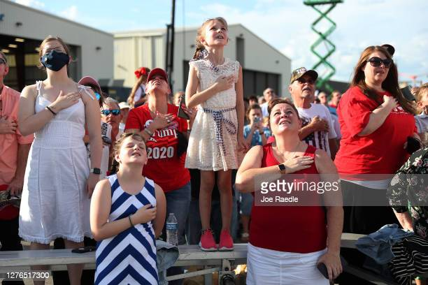 People stand for the Pledge of Allegiance before the arrival of US President Donald Trump for the The Great American Comeback Rally at Cecil Airport...
