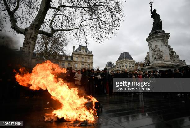 People stand guard by a bin set on fire during a demonstration by high school students at place de la Republique in Paris on December 7 2018 to...