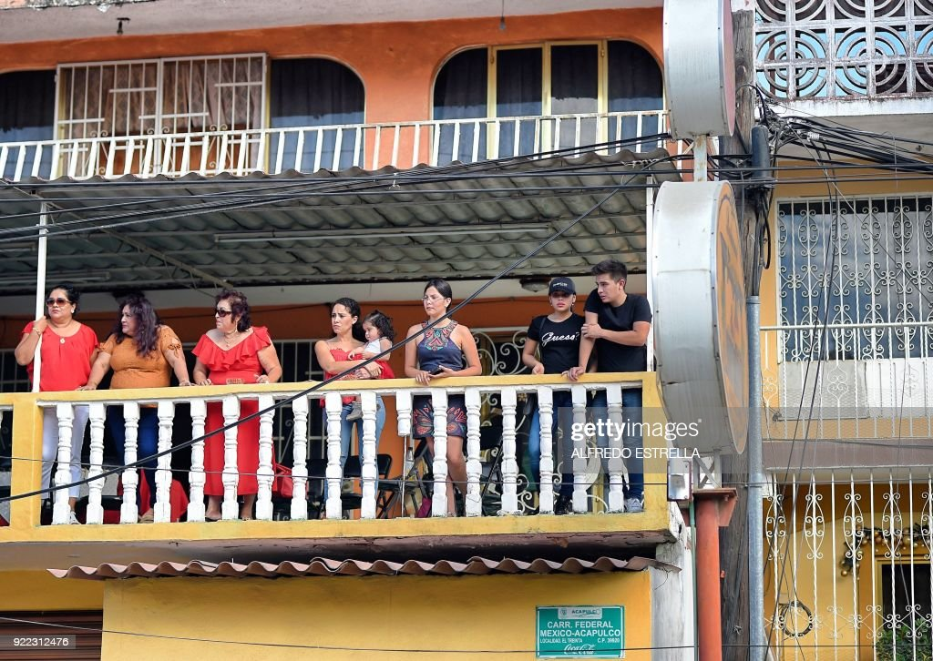 People stand in a balcony at Kilometro 30 community near the Acapulco resort in Guerrero State, Mexico, on February 14, 2018. Violence in the state of Guerrero claimed the lives of two priests on February 5, 2018. / AFP PHOTO / Alfredo ESTRELLA / TO