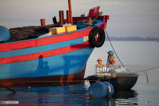 People stand in a bamboo boat next to a fishing trawler at dawn in Tan Quang harbor in Quang Nam province Vietnam on Wednesday June 26 2019 Fishermen...
