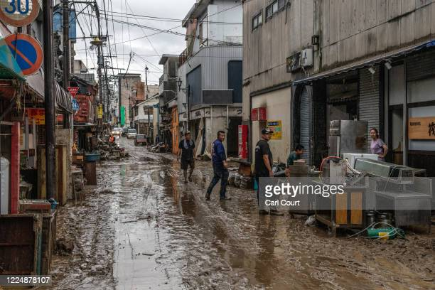 People stand in a flood damaged street after the nearby Kuma River burst its banks, on July 5, 2020 in Hitoyoshi, Japan. Around 16 people are...