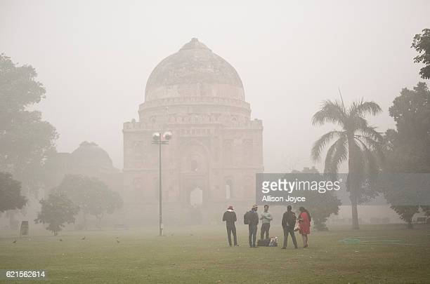 People stand in a park amid heavy dust and smog November 7 2016 in Delhi India People in India's capital city are struggling with heavily polluted...