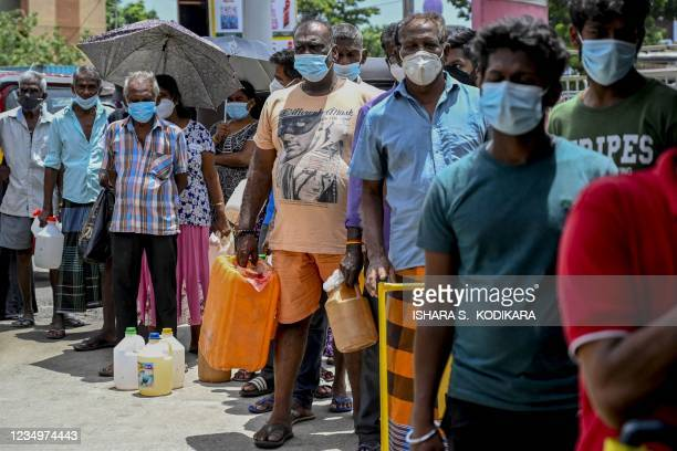 People stand in a queue to buy kerosene oil used in cooking stoves in Colombo on August 31, 2021 following Sri Lanka's declaration of state of...