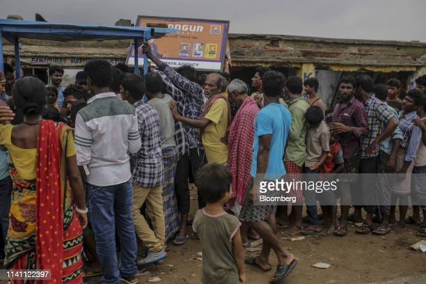 People stand in a queue to collect food after Cyclone Fani passed through Puri Odisha India on Saturday May 4 2019 A category 4 storm with strong...