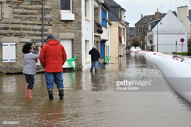 People stand in a street in Pontivy northwestern France flooded by the rising waters of the Blavet river on February 8 2014 Two departments in the...