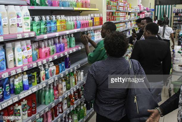 People stand in an isle to buy liquid soaps after the stock of disinfectants ran out at supermarkets in Kenya in Nairobi on March 13, 2020. - Kenya...