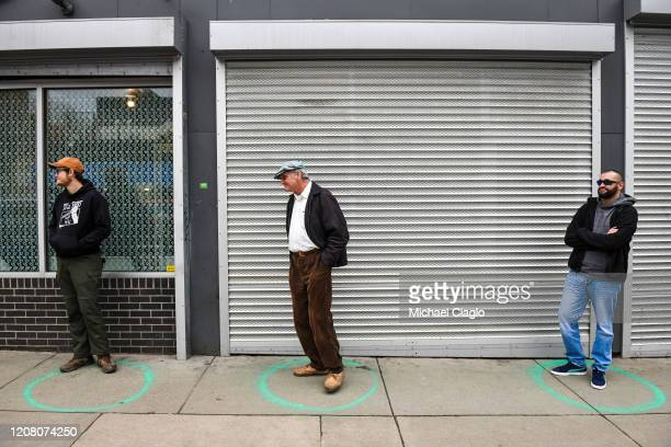 People stand in freshly painted circles sixfeetapart as they wait in a twohour line to buy marijuana products from Good Chemistry on March 23 2020 in...