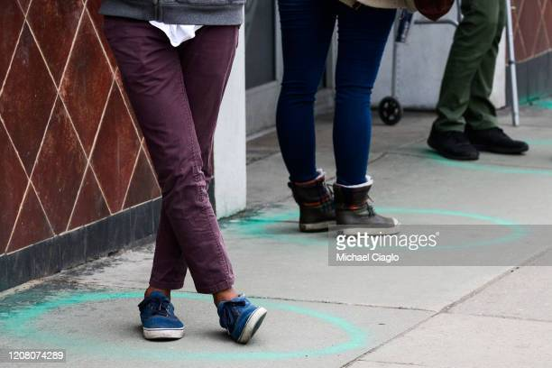 People stand in freshly painted circles, six-feet-apart, as they wait in a two-hour line to buy marijuana products from Good Chemistry on March 23,...