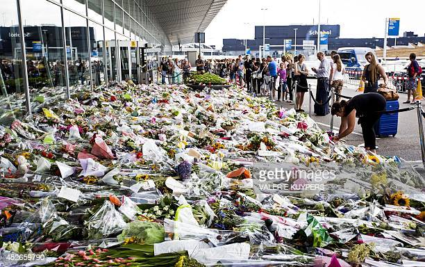 People stand in front bouquets of flowers laying in tribute of the victims of downed Malaysia Airlines flight MH17 on July 25 2014 at the Schiphol...