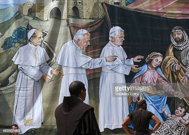 People stand in front of a giant banner featuring Jesus' birth with former Popes Paul VI JeanPaul II and Benedict XVI visiting him on May 23 2014 at...