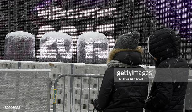 People stand in front of a giant screen reading 'Welcome 2015' on a stage built at the Brandenburg Gate on the eve of New Year's celebrations in...
