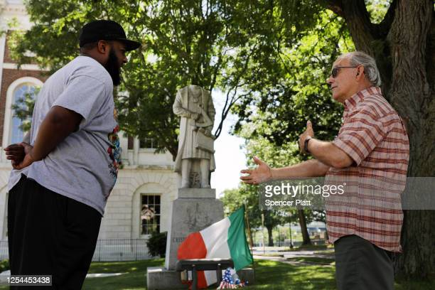 People stand in front of a headless statue of Christopher Columbus outside of Waterbury's city hall on July 05 2020 in Waterbury Connecticut The...
