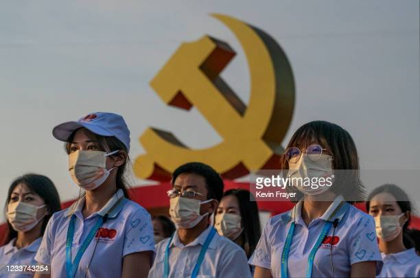 People stand in front of a large Communist Party logo at a ceremony marking the 100th anniversary of the Communist Party on July 1, 2021 at Tiananmen...