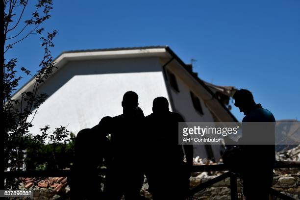 People stand in front of a leaning tower in Amatrice on August 23 2017 a year after a deadly earthquake left nearly 300 people dead and destroyed the...