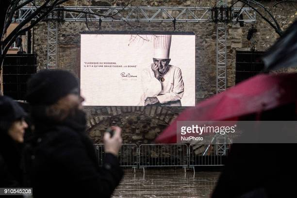 People stand in front of a massive poster of the renowned French chef Paul Bocuse during his funeral in Lyon France on January 26 2018 Bocuse often...