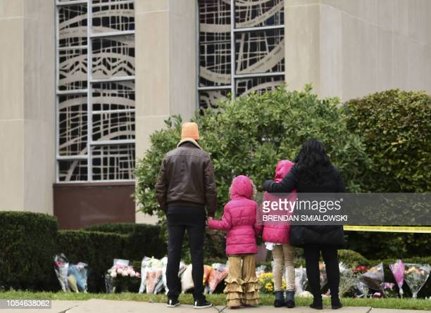 People stand in front of a memorial on October 28 2018 outside of the Tree of Life Synagogue after a shooting there left 11 people dead in the...