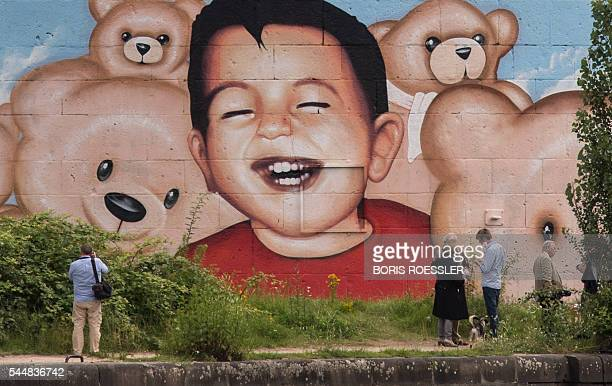 People stand in front of a new graffiti by artists Justus Becker and Oguz Sen depicting the drowned Syrian refugee boy Alan Kurdi at the harbor in...