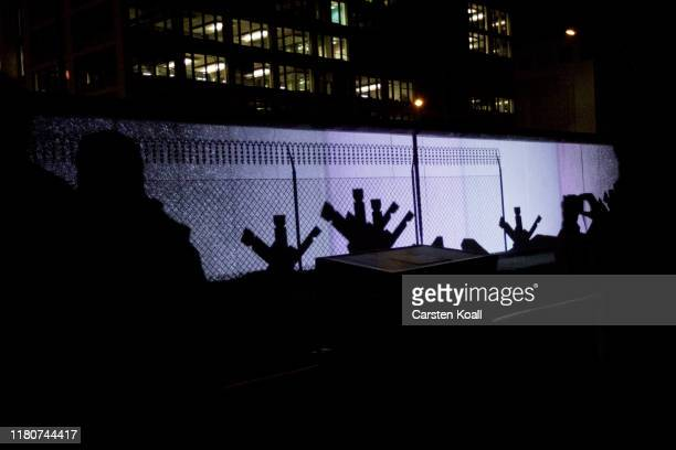 People stand in front of a projection on the East Side Gallery the largest remaining part of the former Berlin Wall during a week of events...