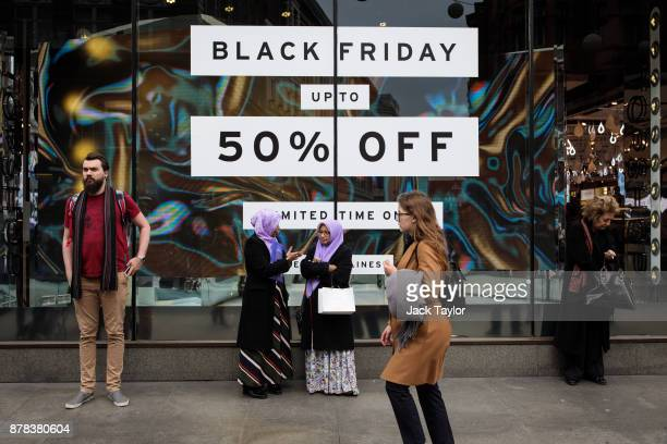 People stand in front of a shop with a Black Friday sale display on Oxford Street on November 24 2017 in London England British retailers offer deals...