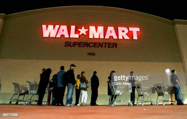 People stand in front of a Walmart store before the doors open at 5am on the day known as 'Black Friday' November 25 2005 in Miami Florida The day...
