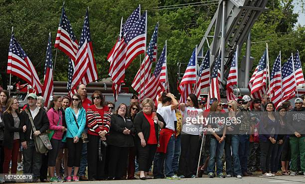 People stand in front of American flags as fire departments from around Texas pay their respects during a parade for the West Memorial Service on...