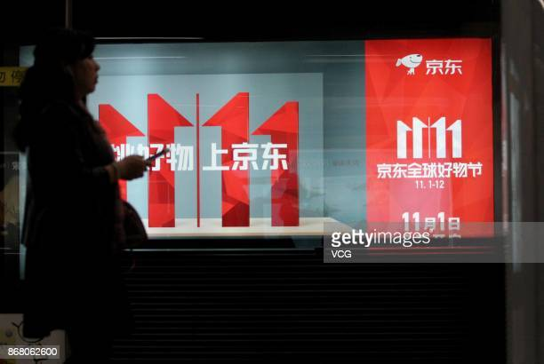 People stand in front of an advertisement for JDcom's Singles' Day sale at a subway station on October 30 2017 in Nanjing China The socalled...