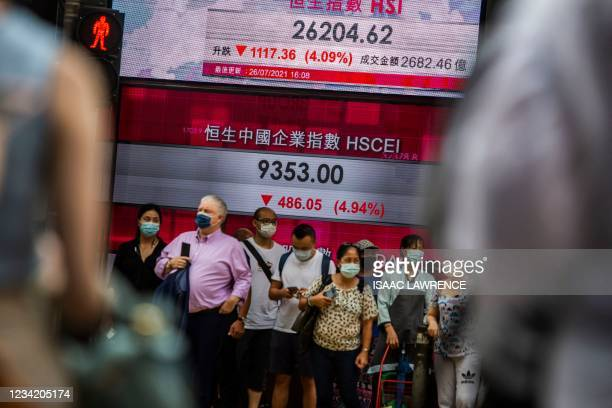 People stand in front of an electronic display showing the Hang Seng Index in the Central district of Hong Kong on July 26 after stocks plunged as...