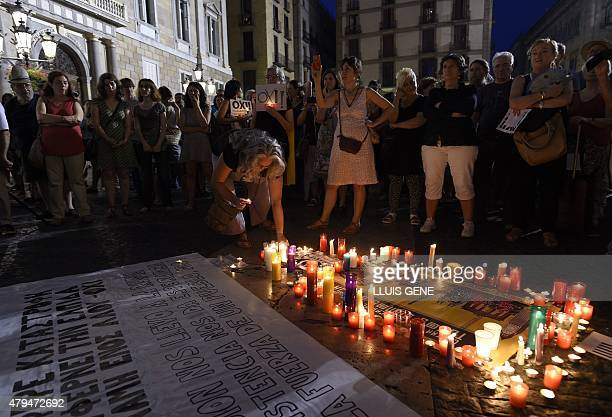 People stand in front of candles displayed next to a message as they take part in a demonstration in support of Greece at Sant Jaume square in...