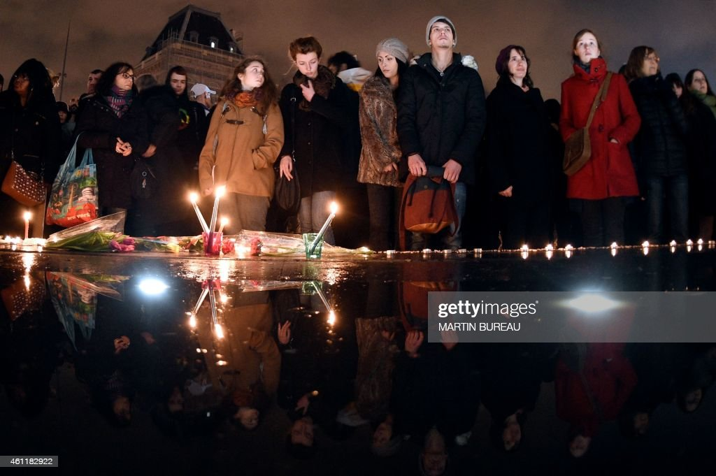 People stand in front of candles during a gathering on the Place de Republique (Republic square) in Paris on January 8, 2015, in tribute to the twelve people killed the day before in an attack by two armed gunmen on the offices of the French satirical newspaper Charlie Hebdo. A huge manhunt for two brothers suspected of massacring 12 people in an Islamist attack at a satirical French weekly zeroed in on a northern town after the discovery of one of the getaway cars. As thousands of police tightened their net, the country marked a rare national day of mourning for Wednesday's bloodbath at Charlie Hebdo magazine in Paris, the worst terrorist attack in France for half a century.