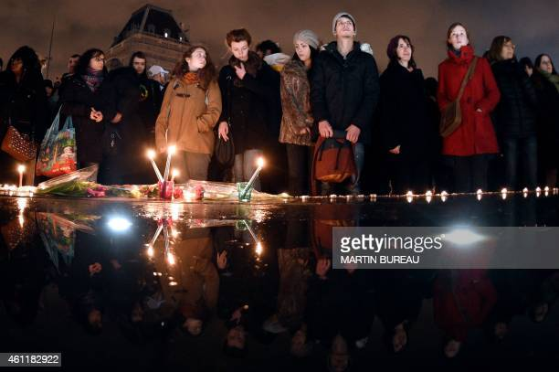 People stand in front of candles during a gathering on the Place de Republique in Paris on January 8 in tribute to the twelve people killed the day...